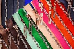 Molte chiusure lampo colorate luminose per i vestiti nel deposito Immagini Stock Libere da Diritti