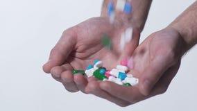 Molte compresse che cadono nelle mani a coppa del paziente, abuso di droga, farmaco stock footage