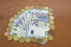 Molte 20 euro banconote e monete su una tavola di legno Fotografia Stock