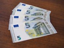 Molte fatture in cinque euro si sono sparse fuori sul ventilatore da tavolo fotografia stock