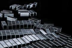Molte graffette metalliche delle ricariche sullo scrittorio nero moderno del lavoro - organizzare e rifornimento per la scrittura fotografie stock