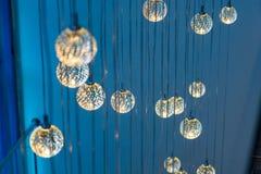 Molte lampade di ardore rotonde che appendono su un fondo blu fotografia stock libera da diritti