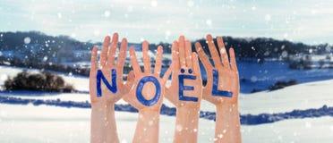 Molte mani che costruiscono Noel Means Christmas, paesaggio di inverno come fondo immagine stock