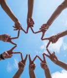 Molte mani che fanno i segni di pace sotto il cielo fotografia stock
