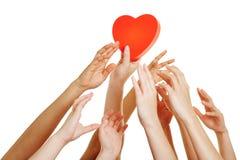 Molte mani che raggiungono per il cuore rosso Fotografie Stock
