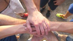Molte mani del maschio che si riuniscono Gruppo degli atleti che un armi all'aperto Gruppo di persone che si prendono per mano in archivi video