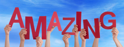 Molte mani della gente tengono il cielo blu stupefacente di parola rossa Fotografia Stock Libera da Diritti