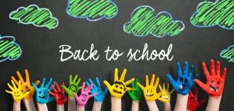 Molte mani dipinte dei bambini con gli smiley e il ` del messaggio di nuovo al ` della scuola fotografia stock libera da diritti