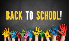 Molte mani dipinte dei bambini con il messaggio & il x22; di nuovo alla scuola! & x22; su una lavagna immagine stock