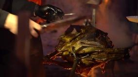 Molte mani hanno tagliato i pezzi della carne dalla carcassa dell'arrosto maiale alla notte al rallentatore archivi video