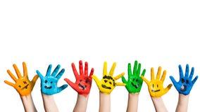 Molte mani variopinte con gli smiley Immagine Stock Libera da Diritti