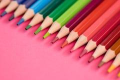 Molte matite colorate differenti che si trovano sul fondo rosa in Wave Fotografia Stock Libera da Diritti