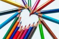 Molte matite colorate differenti su fondo di carta Fotografia Stock