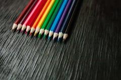 Molte matite colorate su un fondo nero Nuove matite Immagini Stock Libere da Diritti
