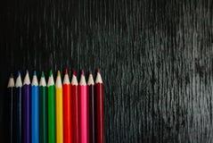 Molte matite colorate su un fondo nero Nuove matite Immagine Stock