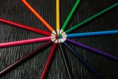 Molte matite colorate su un fondo nero Nuove matite Immagini Stock