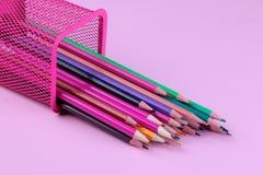 Molte matite multicolori cadono dal vetro su un fondo rosa Rifornimenti di banco immagine stock