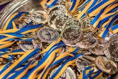 Molte medaglie di argento con i nastri blu su un vassoio d'argento, premi dei campioni, risultati di sport, secondo posto, premio Immagine Stock