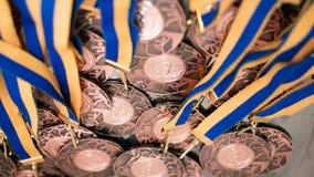 Molte medaglie di bronzo con i nastri blu gialli su un vassoio d'argento Fotografia Stock Libera da Diritti