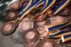 Molte medaglie di bronzo con i nastri blu gialli su un vassoio d'argento Immagine Stock