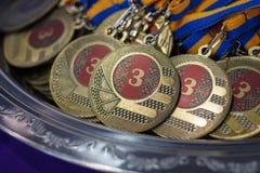 Molte medaglie di bronzo con i nastri di rame ed i nastri blu gialli su un vassoio d'argento, premi dei campioni, risultati nello Fotografie Stock