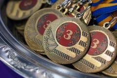 Molte medaglie di bronzo con i nastri di rame ed i nastri blu gialli su un vassoio d'argento, premi dei campioni, risultati nello Fotografia Stock