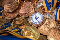 Molte medaglie di bronzo con i nastri di rame ed i nastri blu gialli su un vassoio d'argento, premi dei campioni, risultati nello Immagine Stock Libera da Diritti