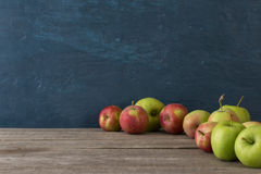 Molte mele sulla tavola di legno su fondo blu Immagini Stock