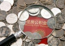 Molte monete e lente sui precedenti di accumulazione dell'alloggio costituiscono un fondo per il libretto bancario Fotografia Stock Libera da Diritti