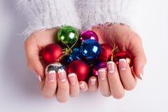 Molte palle variopinte di Natale in mani femminili Immagini Stock