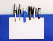 Molte penne che fermano il biglietto da visita con una graffetta bianco Fotografia Stock