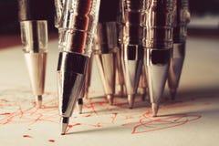 Molte penne rosse scrivono simultaneamente su Libro Bianco, tante linee rosse le tracce della penna Fotografia Stock