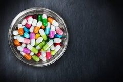 Molte pillole colorate differenti sul nero Fotografia Stock Libera da Diritti