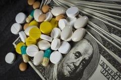 Molte pillole sopra su un mucchio dei dollari fotografie stock