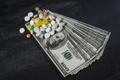 Molte pillole sopra su un mucchio dei dollari fotografie stock libere da diritti