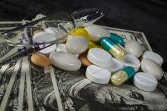 Molte pillole sopra su un mucchio dei dollari immagini stock libere da diritti