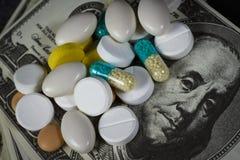 Molte pillole sopra su un mucchio dei dollari immagini stock