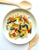 Molte pillole su un piatto bianco immagini stock