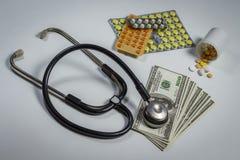 Molte pillole, uno stetoscopio e soldi su una tavola fotografie stock