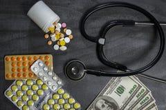 Molte pillole, uno stetoscopio e soldi su una tavola fotografia stock libera da diritti