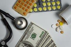 Molte pillole, uno stetoscopio e soldi su una tavola fotografia stock
