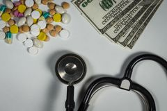 Molte pillole, uno stetoscopio e soldi su una tavola immagini stock