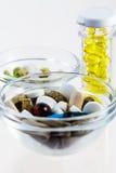 Molte pillole variopinte in ciotole di vetro e bottiglia Immagini Stock