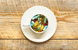 Molte pillole variopinte in tazza sopra wodden la tavola Fotografie Stock Libere da Diritti