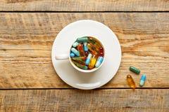 Molte pillole variopinte in tazza sopra wodden la tavola Immagine Stock