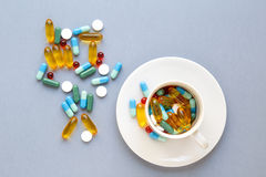 Molte pillole variopinte in tazza su fondo grigio Fotografia Stock Libera da Diritti