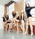 Molte ragazze che si preparano nel balletto dello studio, rinforzo sexy delle gambe lunghe della donna, tuta nera sessuale d'uso Fotografia Stock