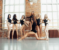 Molte ragazze che si preparano nel balletto dello studio, rinforzo sexy delle gambe lunghe della donna, tuta nera sessuale d'uso Fotografie Stock Libere da Diritti