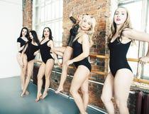 Molte ragazze che si preparano nel balletto dello studio, rinforzo sexy delle gambe lunghe della donna, tuta nera sessuale d'uso, immagini stock libere da diritti