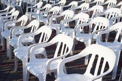 Molte sedie di plastica bianche, esposte un giorno soleggiato all'aperto, per l'evento fotografia stock libera da diritti